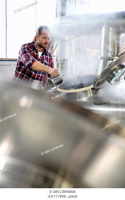 Male Brewery Worker Checking Fermentation Process In Steel Vat