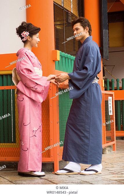 Young couple in kimono visiting Shinto shrine