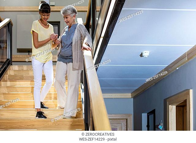 Nurse helping senior woman to walk down the stairs