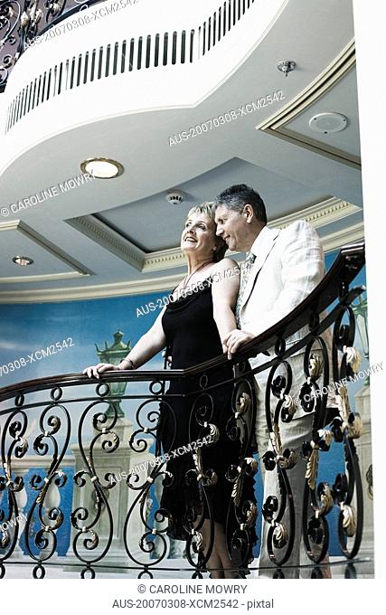 Mature woman and a senior man standing at the balcony of a ship