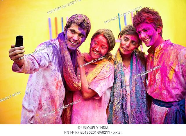 Friends taking picture of themselves with a mobile phone during Holi
