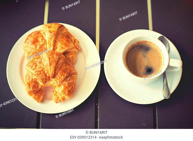 Croissant Breakfast served with black coffee and a breakfast menu, such as orange juice, jam, eggs, filling it