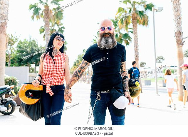 Portrait of mature hipster couple strolling on sidewalk, Valencia, Spain