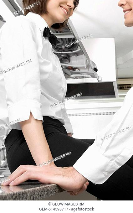 Male and a female waiters romancing in the kitchen