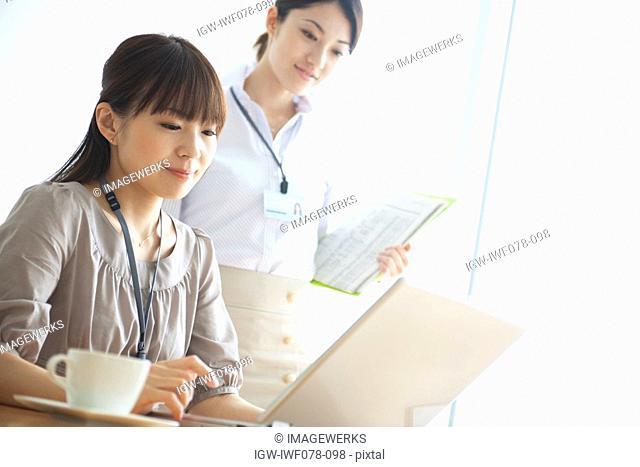 Japan, Osaka Prefecture, Businesswomen using laptop, looking down