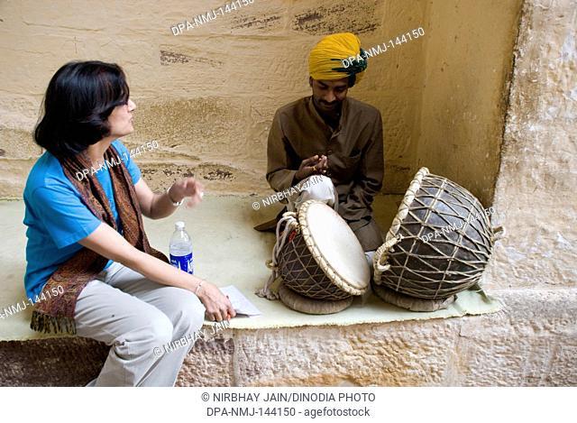A Young lady watching musician who playing drums at Mehrang Garh fort at Jodhpur ; Rajasthan ; India NO MR