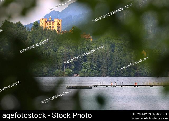 12 June 2021, Bavaria, Schwangau: Excursionists enjoy the sunshine in front of Hohenschwangau Castle on a footbridge at the Alpsee