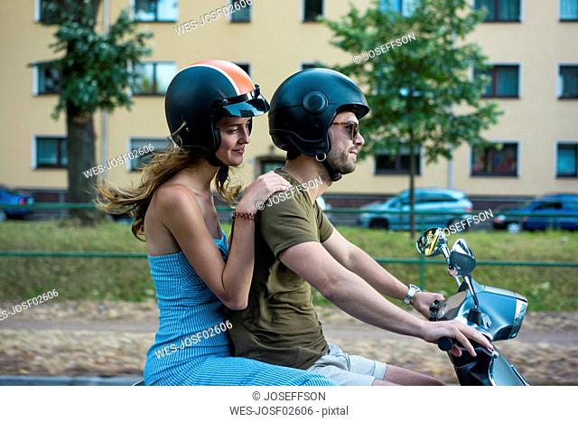 Couple riding motor scooter in the city