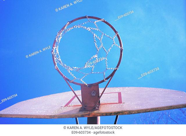 Basketball hoop seen from below, against almost-cloudless blue sky