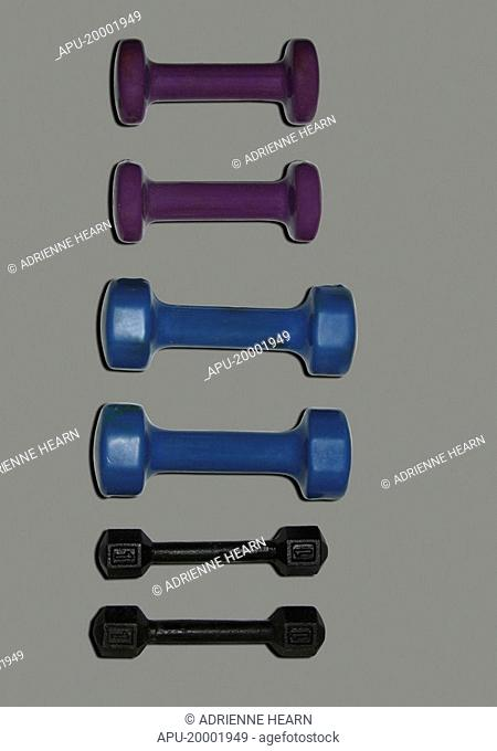 Three sets of free weights on plain background