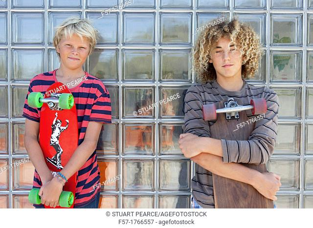 Teenage boys holding their longboards