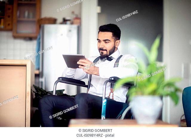 Businessman using digital tablet in wheelchair