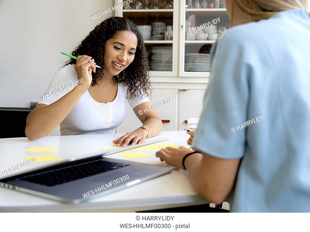 Two friends working at home together, taking notes