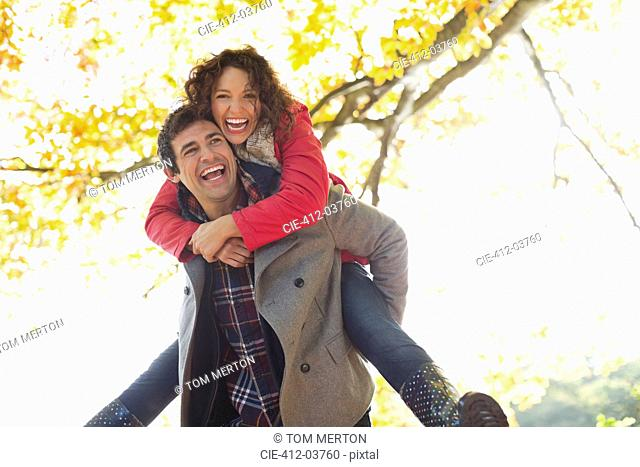Man carrying girlfriend piggyback in park