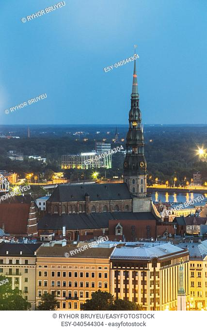 Riga, Latvia. Aerial View Of Cityscape In Summer Evening Or Night Lights Illumination. Top View Of St. Peter's Church. Blue Hour. Famous Landmark