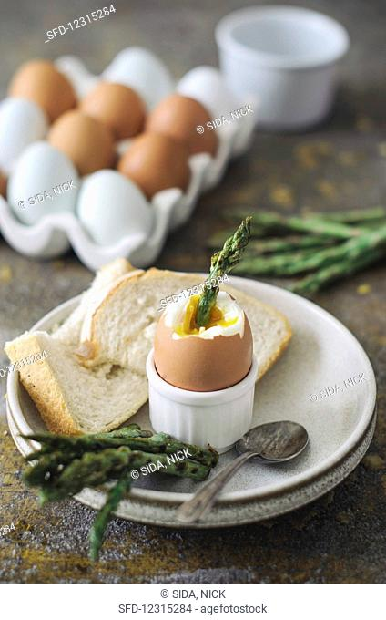 A soft-boiled egg with asparagus and toast soldiers