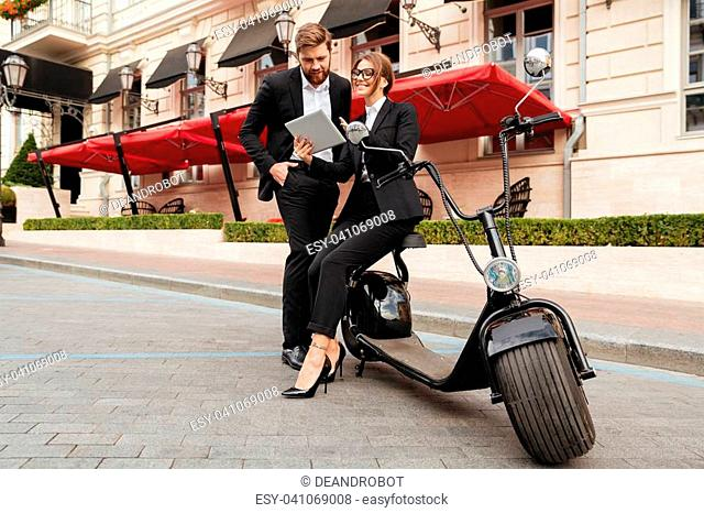 Full length portrait of an attractive successful couple in smart clothes standing and using tablet computer on a city street while leaning on a motor bicycle