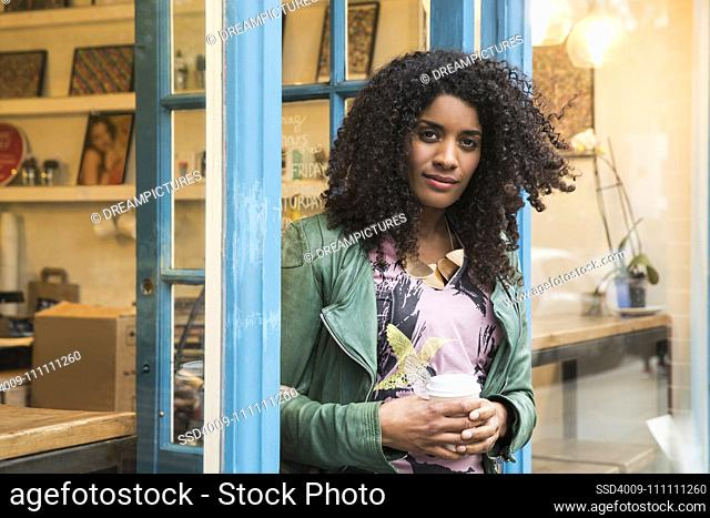 Woman walking out of cafe with coffee in hand