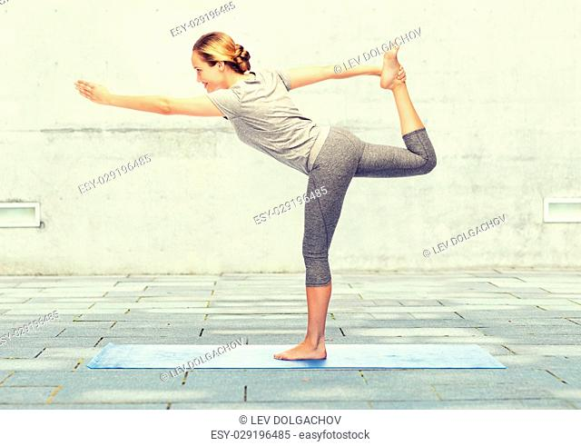 fitness, sport, people and healthy lifestyle concept - woman making yoga in lord of the dance pose on mat over urban street background