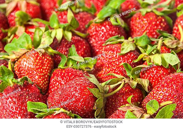 Abstract background of red strawberries with green tails