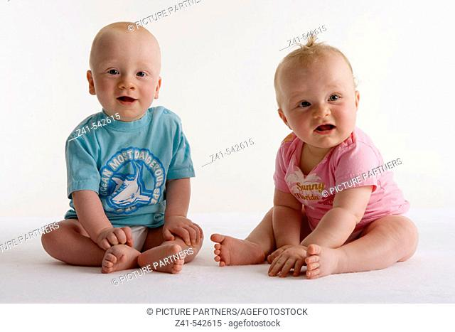 Two toddlers sitting on the floor
