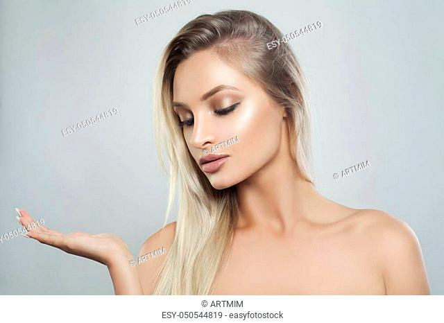 Young Perfect Woman with Natural Makeup, Healthy Skin and Blonde Hair Showing Empty Copy Space on the Open Hand. Facial treatment, Cosmetology, Beauty