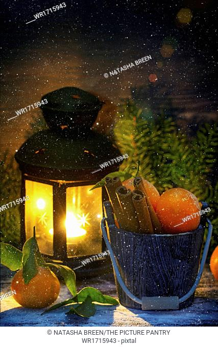 Wooden bucket with tangerines and cinnamon sticks over wooden background with burning lantern, falling snow and Christmas tree