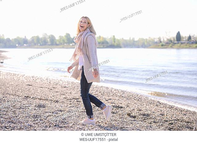 Happy mature woman walking at the riverside