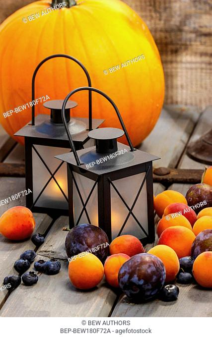 Autumn fruits and traditional lanterns on wooden table. Seasonal decoration