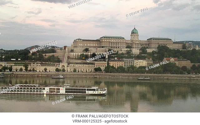 Cruise going down the Danibe river in Budapest Hungary. It is going past the Royal Palace