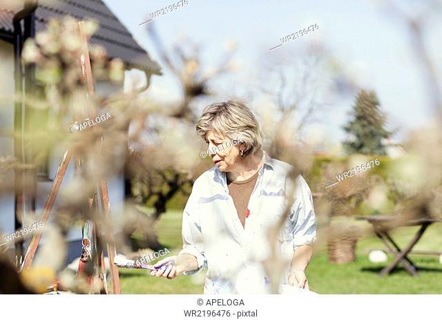 Senior female artist painting on easel in backyard