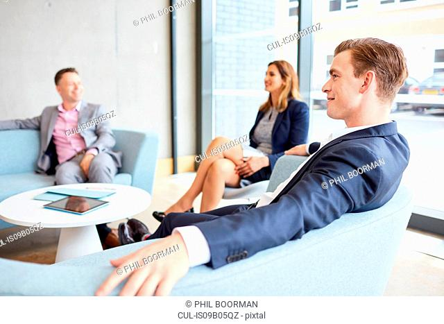 Businessmen and businesswoman meeting on office sofas