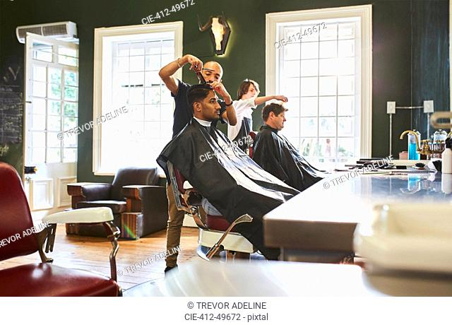 Male barber cutting hair of customer in barbershop