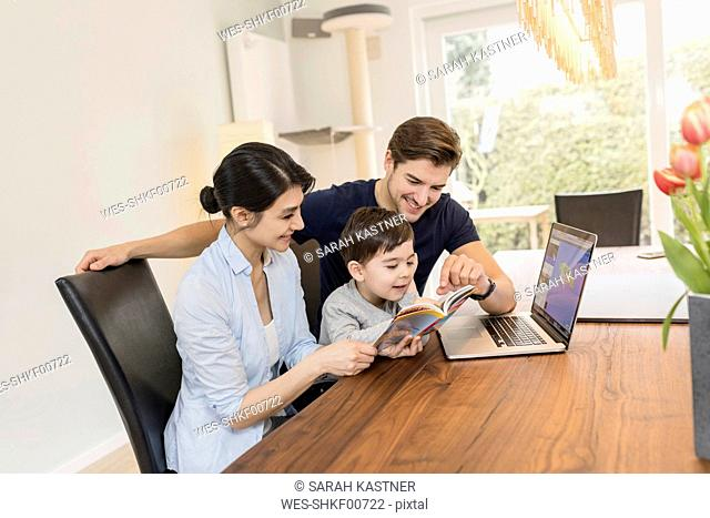 Family with laptop and guidebook planning vacation at home