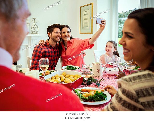 Couple with camera phone taking selfie at Christmas dinner table