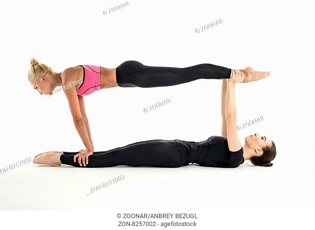 Strong athletic girl in black leggings. Perform complex gymnastic exercise. The first girl lying on her back vityanuv hands up as a prop