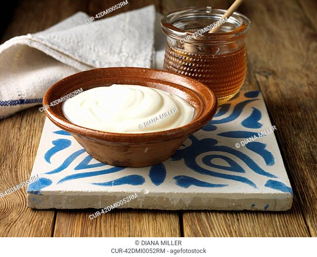 Organic Greek Yoghurt in a Terracota Bowl with a jar of Greek Honey on a blue and whiteceramic tile with a napkin in the background