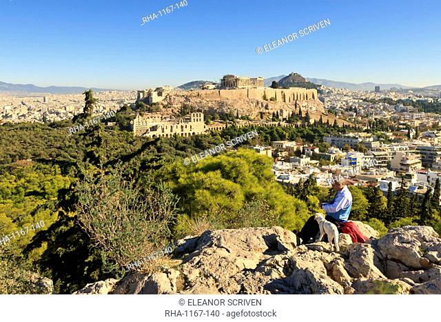 Man with dog reads a book on the Filopappos Hill, with a view to the Parthenon and Acropolis, Athens, Greece, Europe