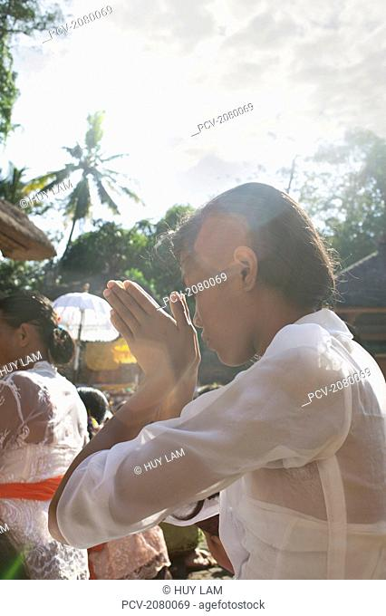 Young woman praying during Kuningan Festival; Bali, Indonesia