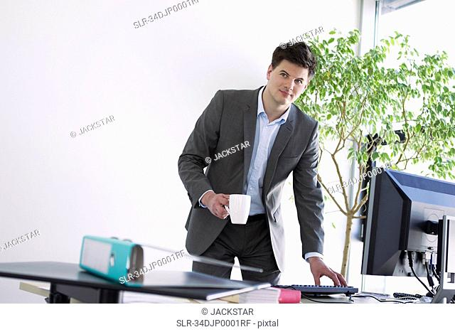 Businessman with cup of coffee at desk