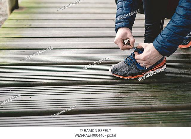 Jogger tying his sneakers on a wooden floor