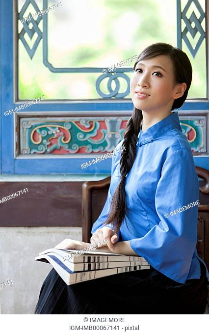 Young woman with cheongsam sitting and looking away