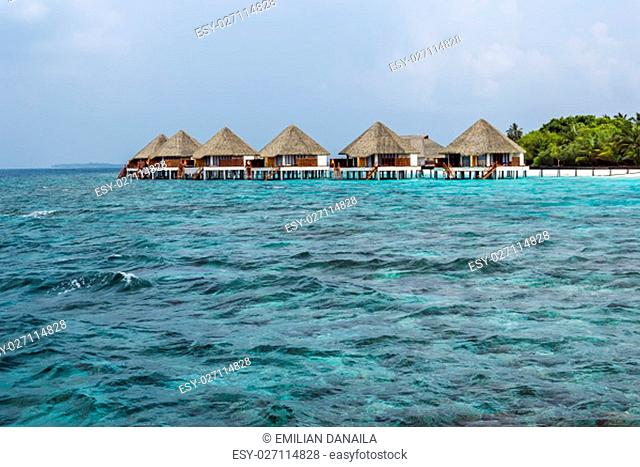 Typically Maldivian Landscape with turquoise ocean, blue sky, white sand beach and beach villas