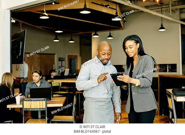 Waiter and businesswoman using digital tablet in cafe