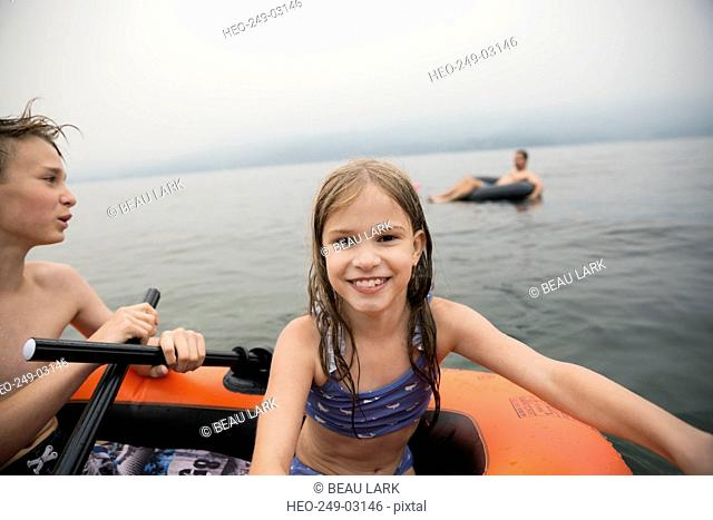 Portrait smiling girl in inflatable raft on lake