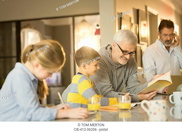 Male gay parents helping children with homework at counter