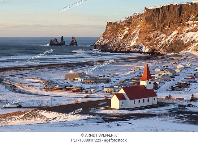 Reynisdrangar sea stacks and the Vík church at the village Vík í Mýrdal in winter, Iceland