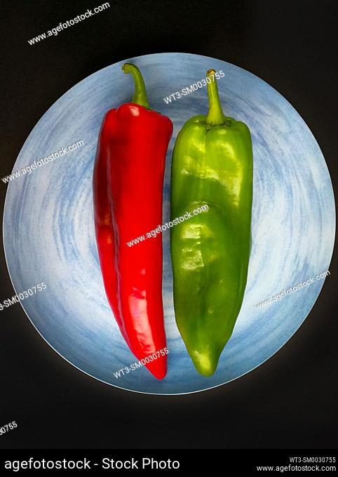 A red pepper and a green pepper on a blue plate