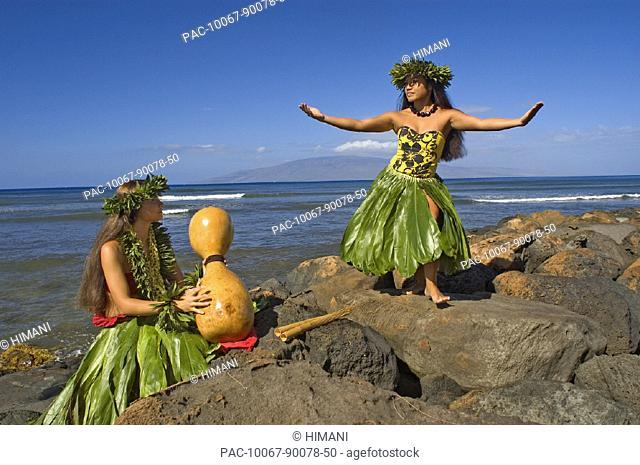 Two hula dancers in traditional outfits on rocky shore, one dancing while the other plays ipu
