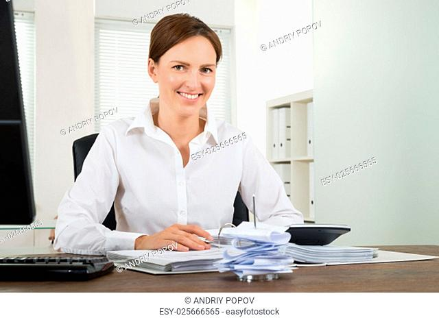 Happy Businesswoman Calculating Bills With Calculator At Desk